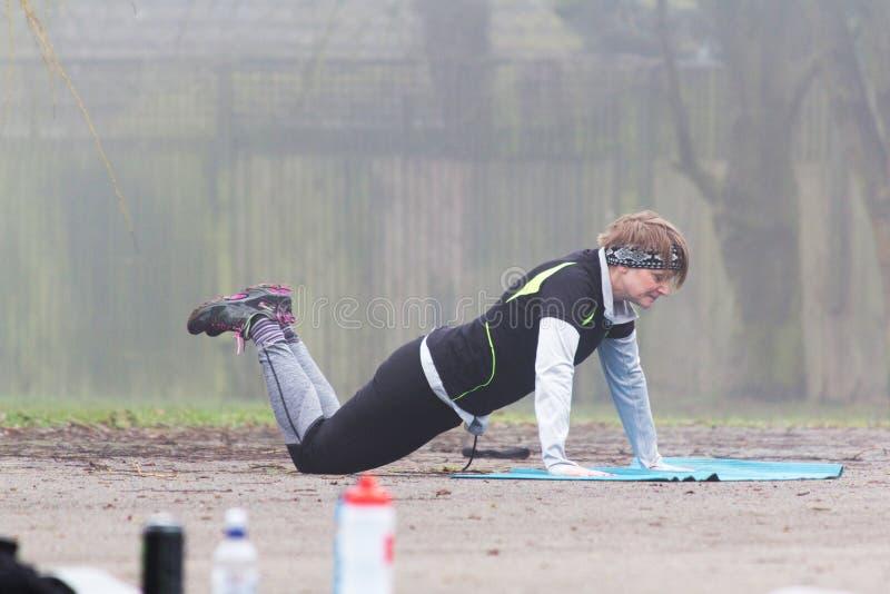 Делать людей держит подходящую тренировку в парке стоковое фото