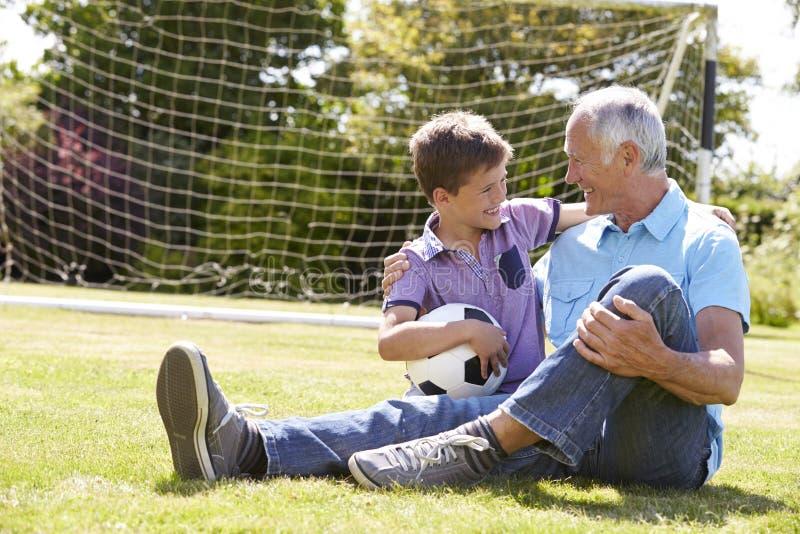 Дед и внук играя футбол в саде стоковое фото