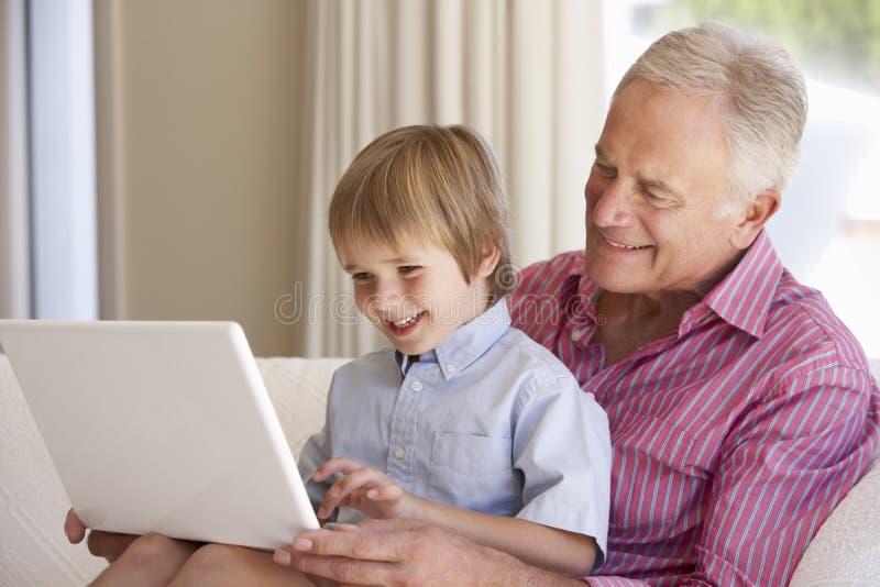 Дед и внук используя компьтер-книжку дома стоковая фотография