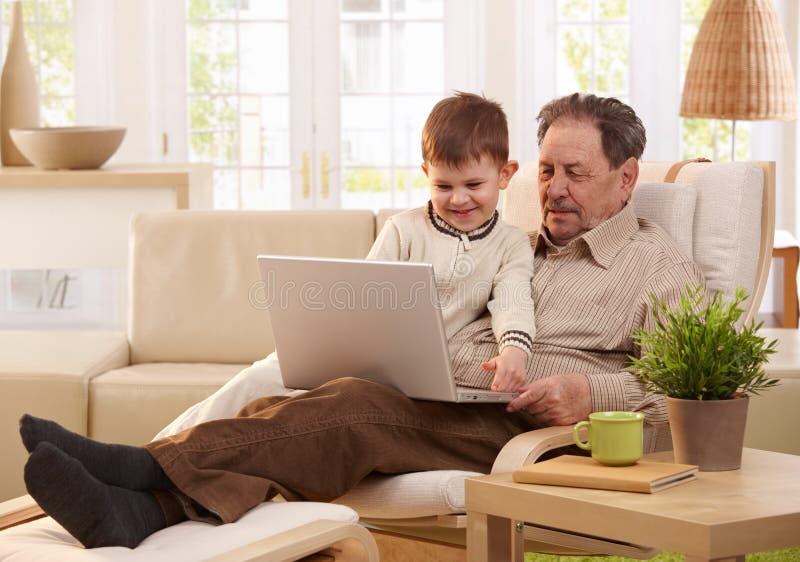 Дед и внук используя компьютер совместно стоковое фото