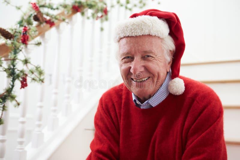 Дед нося шляпу Санты сидя на лестницах на рождестве стоковое изображение