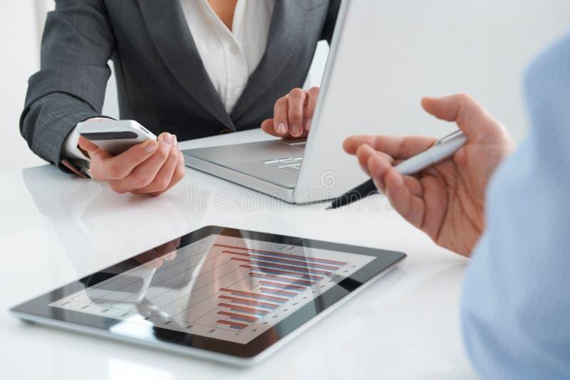 Деловая встреча используя таблетку, компьтер-книжку и мобильный телефон цифров стоковые изображения