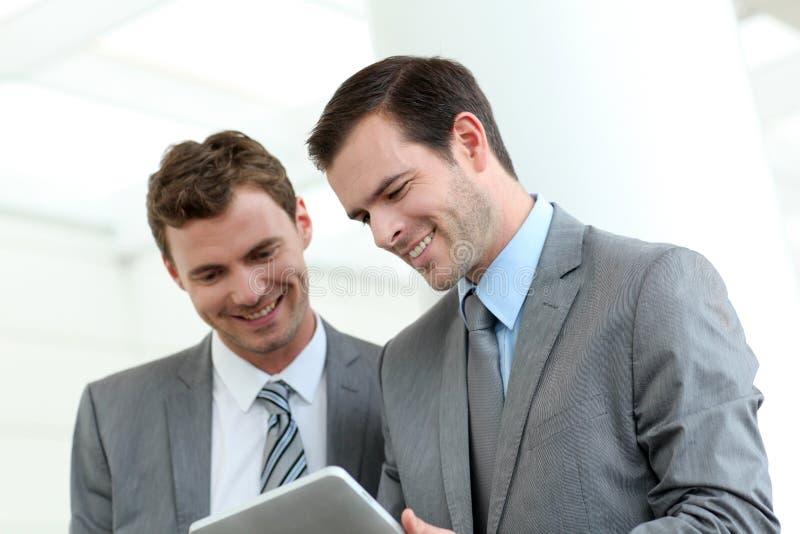 Деловые партнеры используя таблетку в прихожей стоковое фото