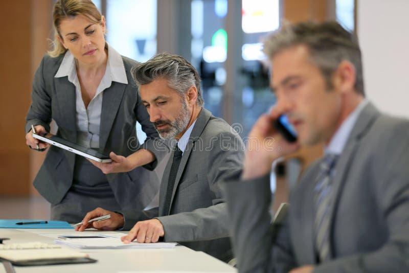Деловые партнеры работая в офисе стоковые изображения rf