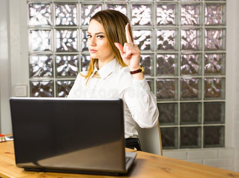 Дело и концепция рекламы - привлекательная молодая женщина с ее пальцем вверх на офисе стоковые изображения