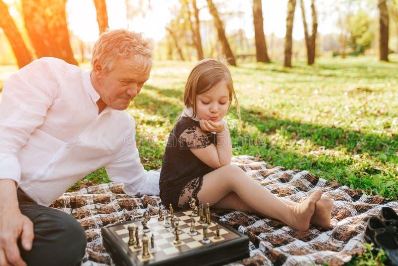 Дед с маленькой девочкой в парке стоковые изображения