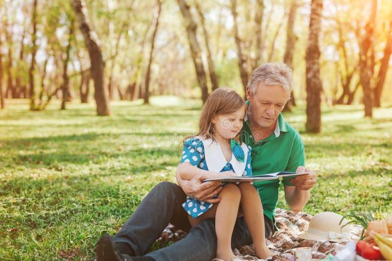 Дед с чтением маленькой девочки стоковые изображения rf