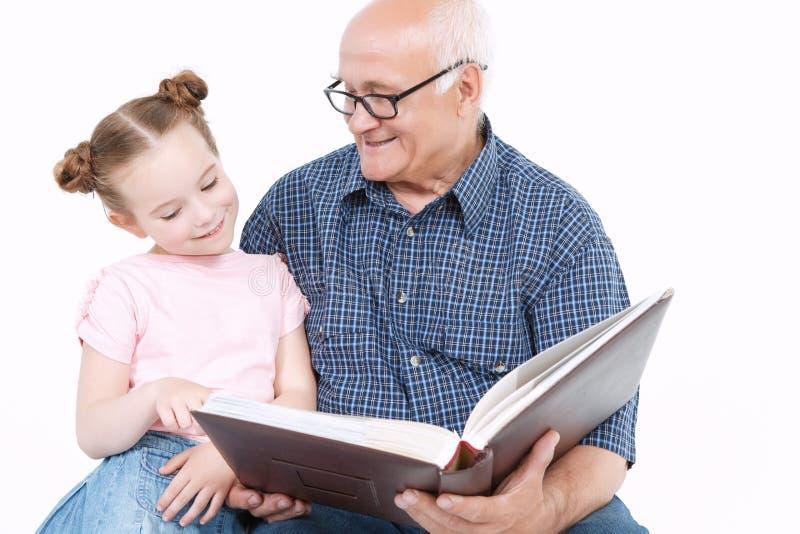 Дед читая книгу с внучкой стоковая фотография rf