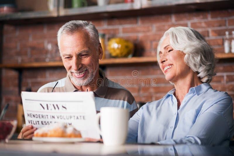 Деды читая газету совместно на кухонном столе стоковые изображения rf