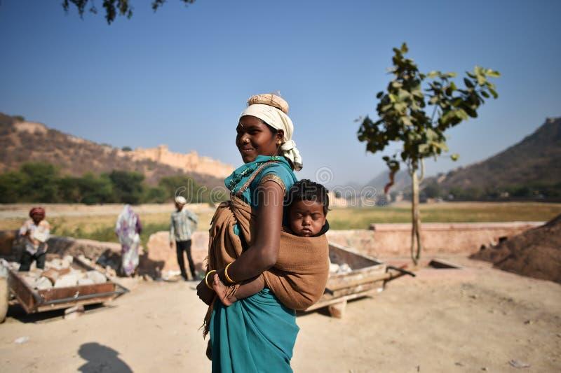 Джайпур, Индия, 1-ое декабря 2017: Женщина работая крепко заботить облицовывает носить ребенка на задней части стоковые фото