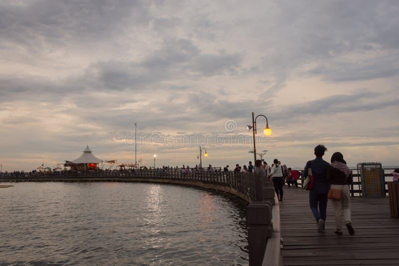 Джакарта, Индонезия - 9-ое декабря 2017: Деятельности при людей с небом сумрака на мосте Ancol любов стоковое изображение rf