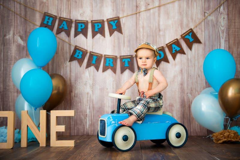 Джентльмен ребенк мальчика в ретро костюме с подтяжками и крышкой сидит на деревянном автомобиле Партия детей с воздушными шарами стоковые изображения rf
