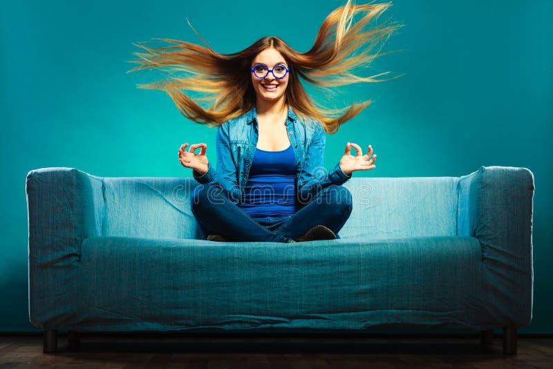 Джинсовая ткань модной девушки нося сидя на кресле стоковая фотография rf