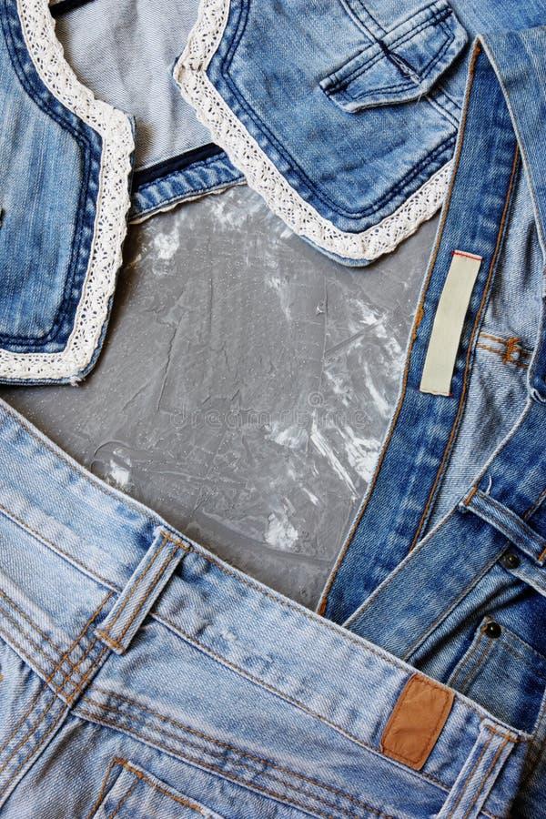 Джинсовая ткань на серой конкретной предпосылке стоковая фотография rf