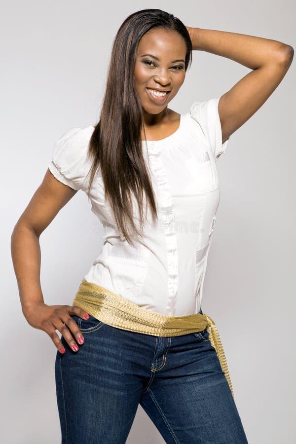 джинсыы девушки афроамериканца голубые молодые стоковое изображение
