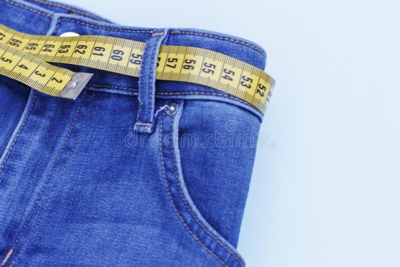 Джинсы и измеряя конец-вверх ленты, концепция здорового образа жизни и теряя вес, космос экземпляра стоковая фотография