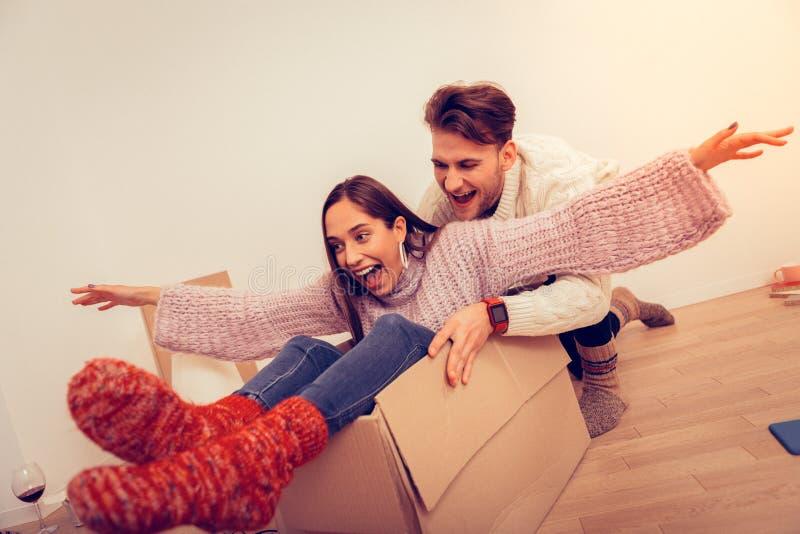 джинсы и свитер Темн-с волосами жены нося сидя в пустой коробке стоковое фото