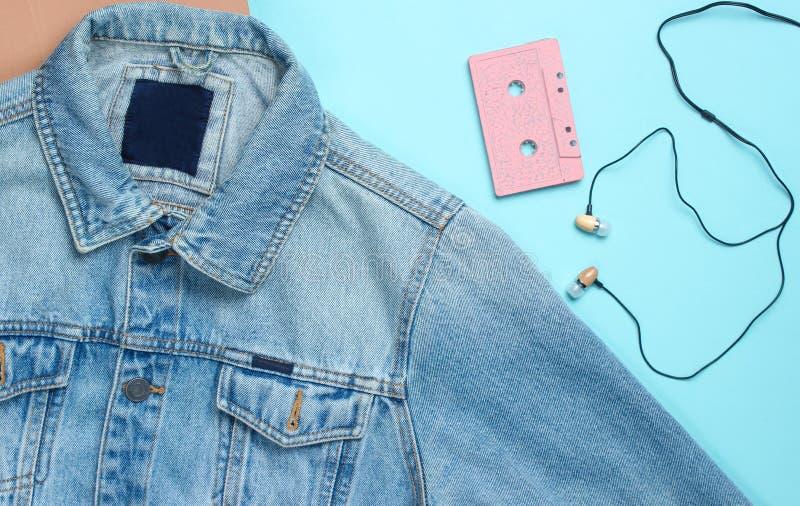 Джинсы куртка, магнитофонная кассета, наушники вакуума на голубой пастельной предпосылке Ретро средства массовой информации, люби стоковое фото