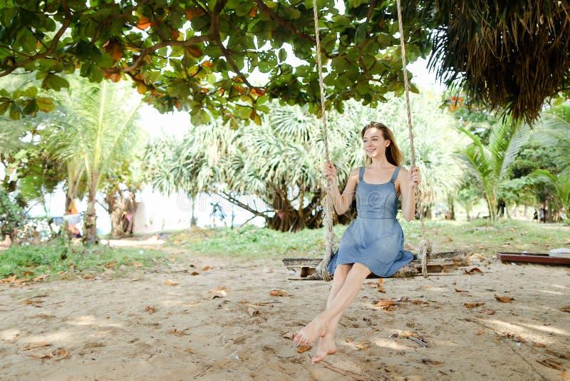 Джинсы молодой красивой женщины нося одевают и едущ на качании, песке в предпосылке стоковое изображение