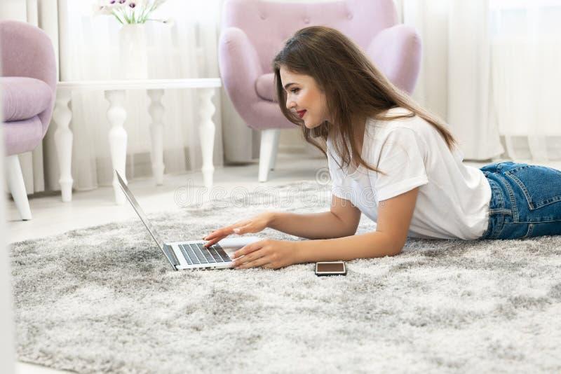 Джинсы привлекательной молодой женщины брюнета нося и белая футболка лежа на поле в яркой гостиной с ее ноутбуком стоковое изображение rf