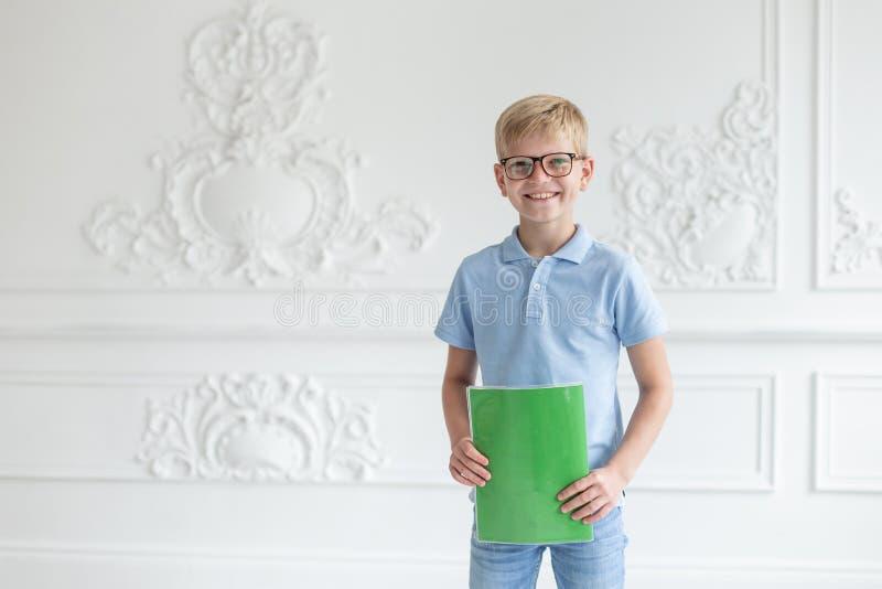 Джинсы школьника нося и голубая футболка представляя на предпосылке белой стены с зеленой тетрадью с прописями в руках стоковое фото