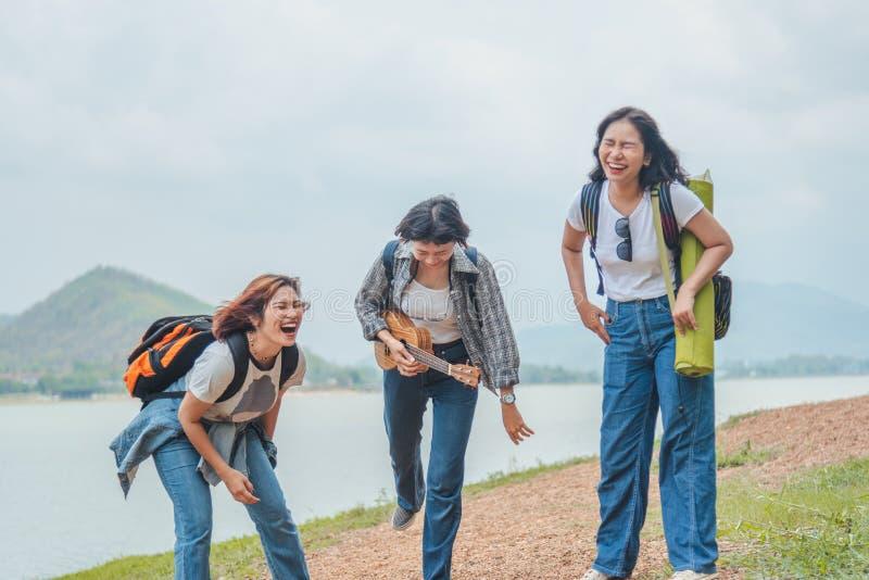 Джунгли с друзьями Группа в составе молодые люди с рюкзаками идя совместно и выглядя счастливый стоковая фотография