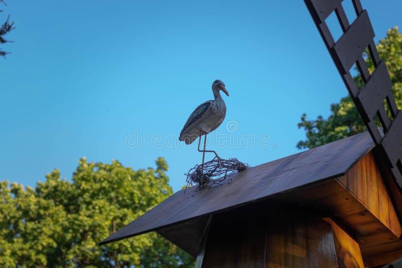 Диаграмма аиста на крыше деревянного дома, на фоне выравниваясь неба стоковое фото rf