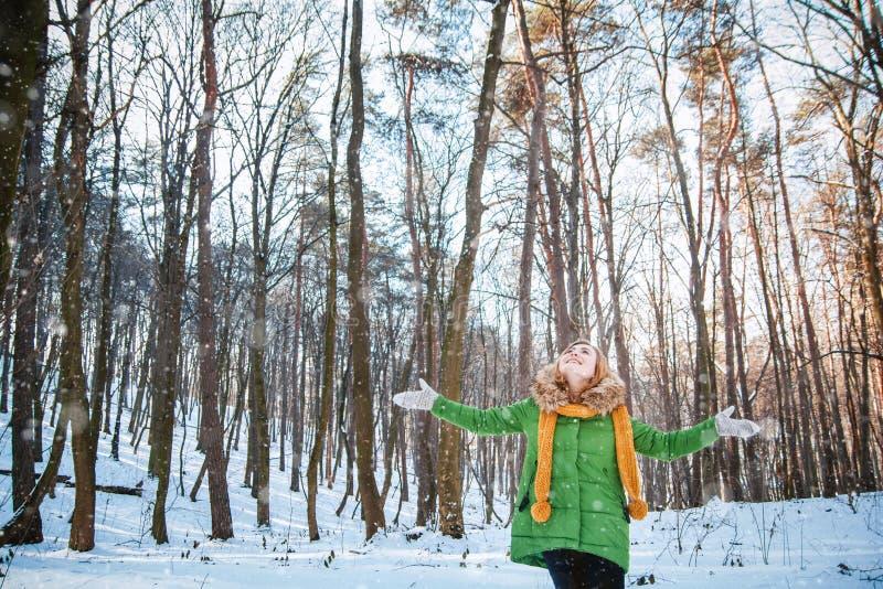Диаграмма девушки в parka, шляпе, пушистых mittens, стоящ с протягиванными оружиями, смотря на солнце в зиме стоковые изображения