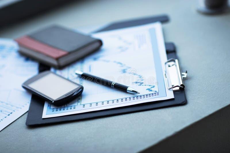 Диаграмма дела с умными телефоном и ручкой Бухгалтерский учет стоковые изображения rf
