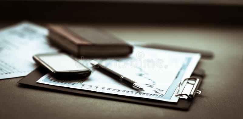 Диаграмма дела с умными телефоном и ручкой проинвестируйте стоковая фотография