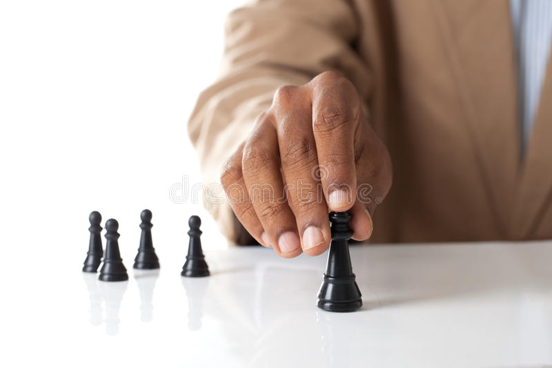 Диаграмма шахмат бизнесмена moving с командой позади - стратегия или стоковые фото