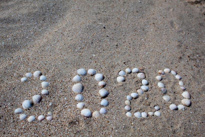 """Диаграмма """"2020 """"положена вне на песок с раковинами стоковое изображение"""