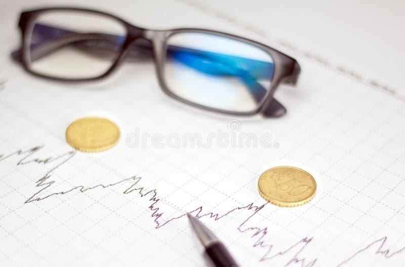 Диаграммы, стекла, калькулятор и монетки на столе офиса стоковое фото rf