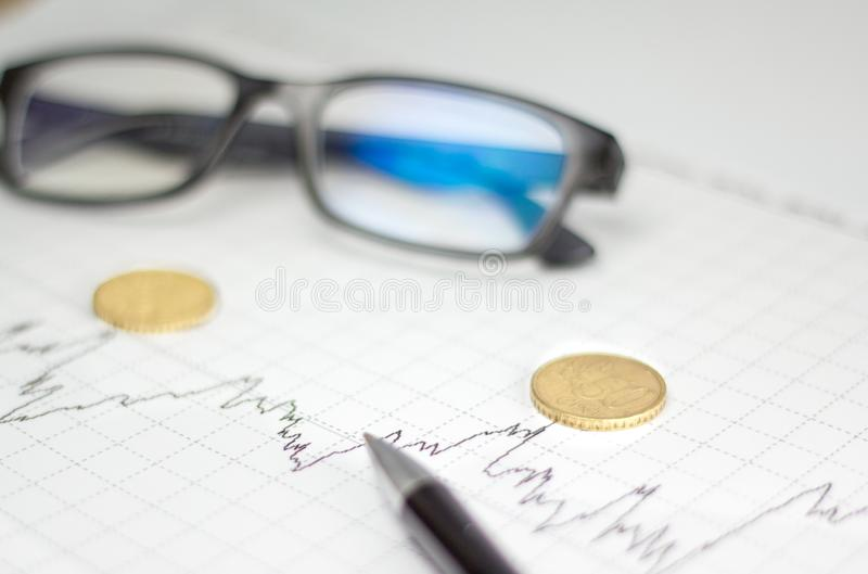 Диаграммы, стекла, калькулятор и монетки на столе офиса стоковая фотография
