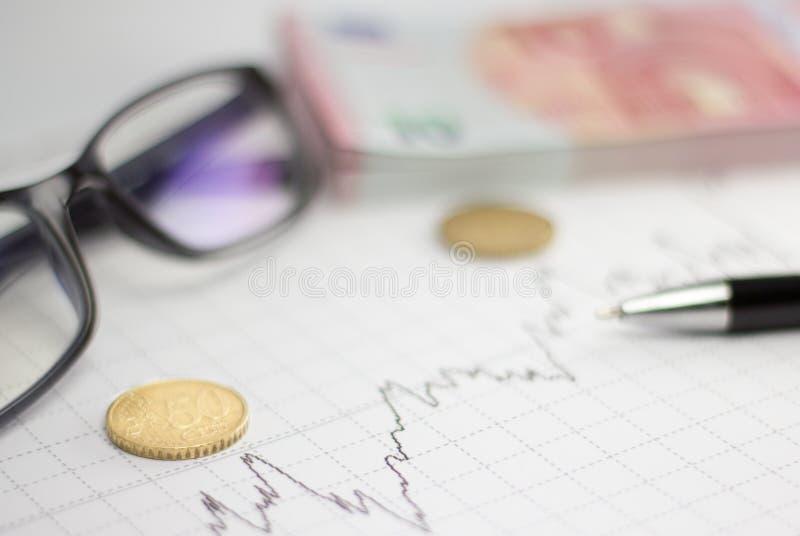 Диаграммы, стекла, калькулятор и монетки на столе офиса стоковые изображения rf