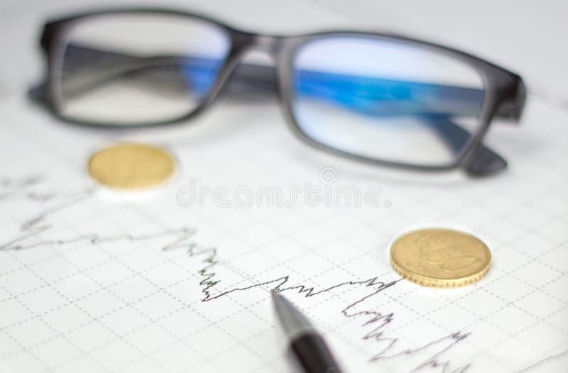 Диаграммы, стекла, калькулятор и монетки на столе офиса стоковая фотография rf
