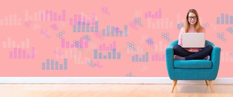 Диаграммы цифров и решетки шестиугольника с женщиной используя ноутбук стоковое изображение