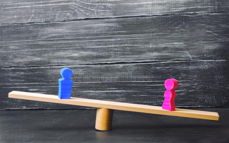 Диаграммы человека и женщины на масштабах концепция неравенства: человек и женщины на весить балансируют, гендерный разрыв в опла стоковое фото rf