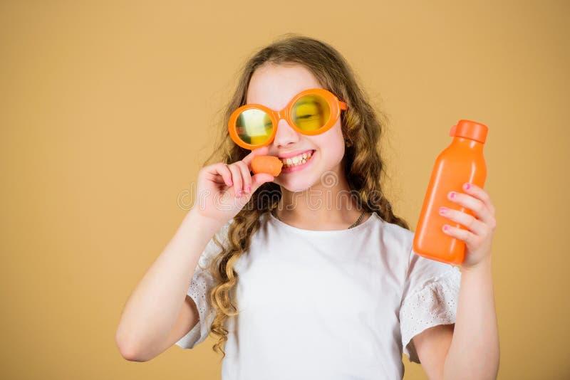 Диета овоща сок моркови счастливого напитка девушки свежий r маленькая девочка в стеклах моды Питание витамина стоковая фотография rf