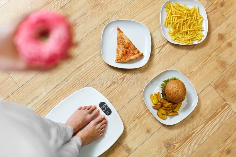 Диета, фаст-фуд Женщина на маштабе Нездоровая высококалорийная вредная пища тучность стоковое изображение
