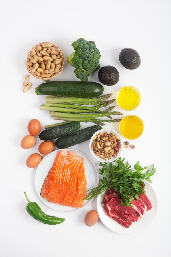 Диета Ketogenic, keto, включая овощи, мясо и рыб, гайки и масло на белой предпосылке стоковые изображения rf