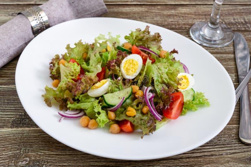 Диетический, вегетарианский салат с яичками триперсток, свежие травы, нуты, красные луки и томаты вишни стоковые изображения