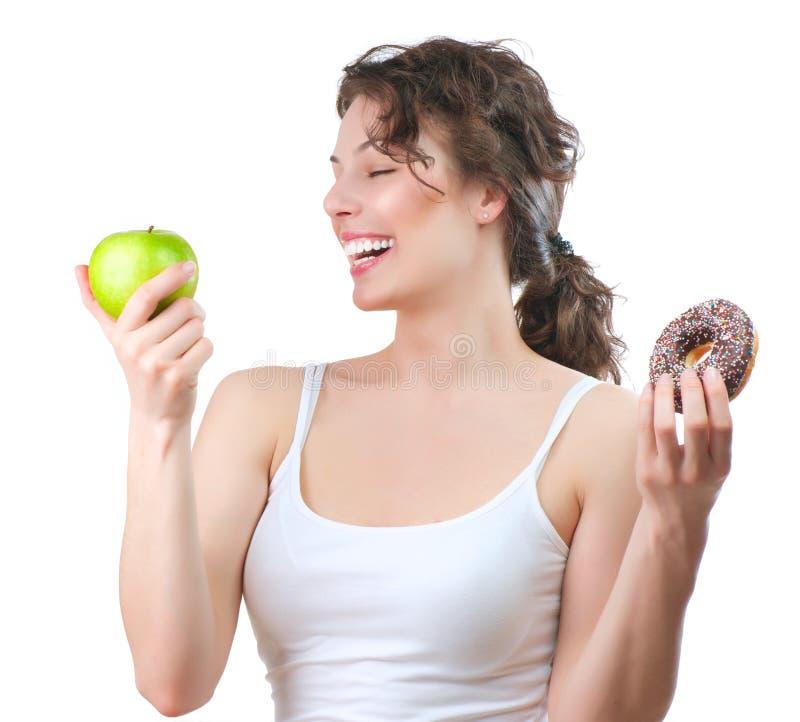 Диетпитание. Молодая женщина выбирая между плодоовощ и донутом стоковые фотографии rf