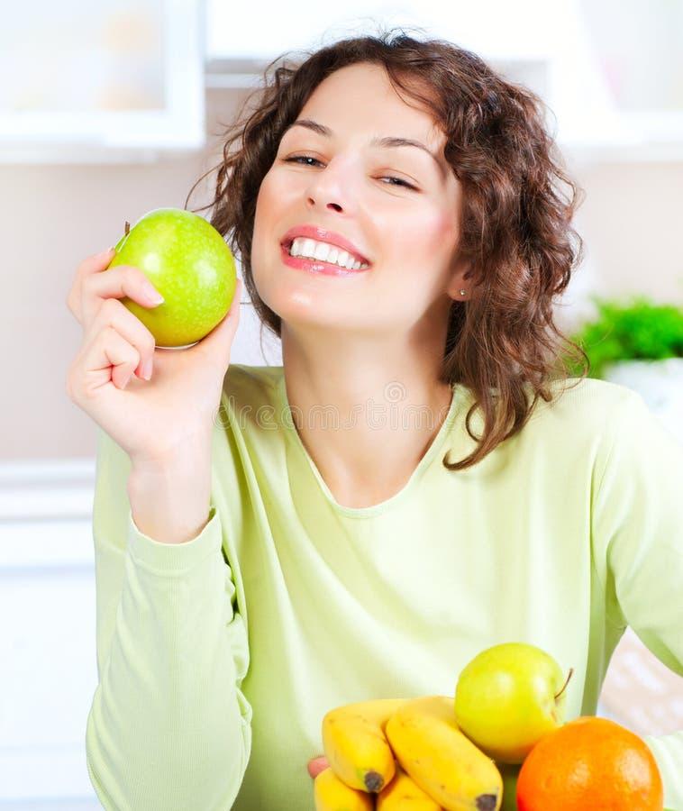 Диетпитание. Молодая женщина есть свежие фрукты стоковое фото rf