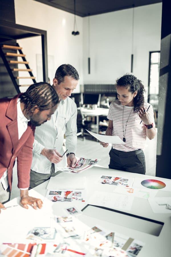 3 дизайнера по интерьеру выбирая цвета для нового проекта стоковая фотография