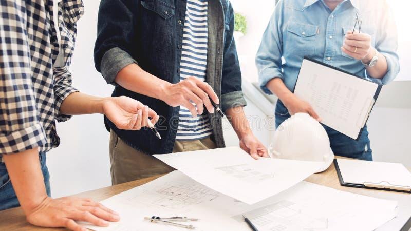 Дизайнеры в офисе работают архитектор светокопии обсуждения на новой сыгранности притяжки дизайна проекта на деревянном столе стоковые изображения rf