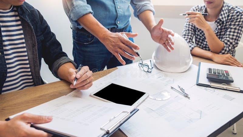 Дизайнеры в офисе работают архитектор светокопии обсуждения на новой сыгранности притяжки дизайна проекта на деревянном столе стоковое изображение