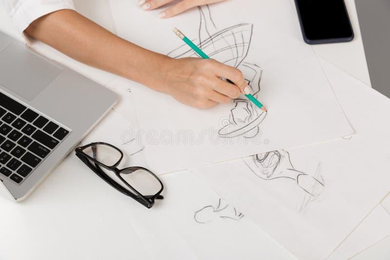 Дизайнер бизнес-леди изолированный над серой предпосылкой стены сидя на чертеже таблицы стоковая фотография rf