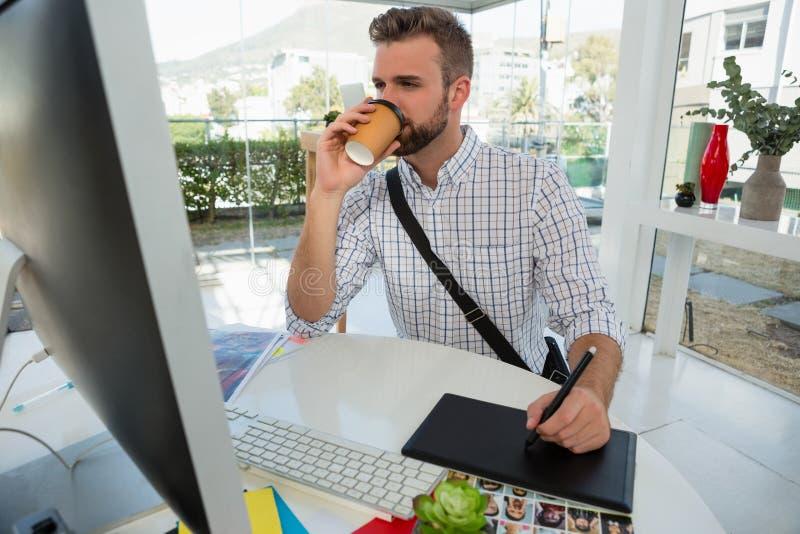 Дизайнер имея сочинительство питья на таблетке графиков стоковые фото