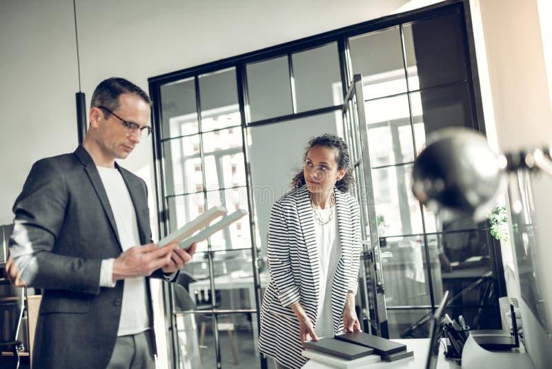 Дизайнер по интерьеру выбирая материалы стоя около секретарши стоковые изображения